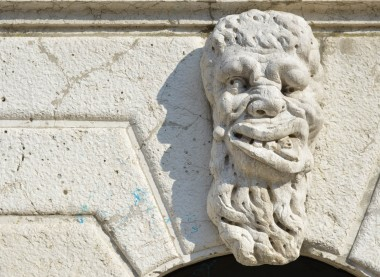 Mascheron a sculpture of a deformed face over a wall in Venice